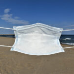 Surgical/medical mask being held up in front of the sea, at the beach, by female adult caucasian hands, following obligation to wear a mask at the beach and in all the pubblic places Italy, pandemic, covid 19 prevention,